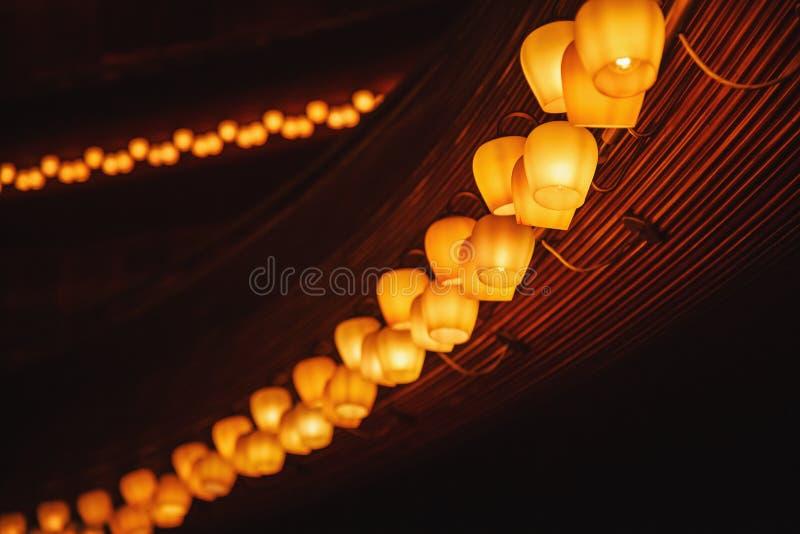 Fila larga de las lámparas del tungsteno en un panel de madera imagen de archivo libre de regalías