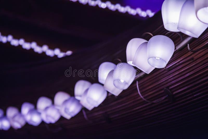 Fila larga de las lámparas del tungsteno en un panel de madera imagen de archivo