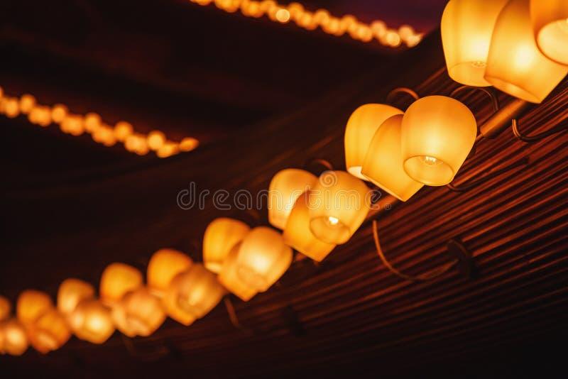 Fila larga de las lámparas del tungsteno en un panel de madera fotografía de archivo
