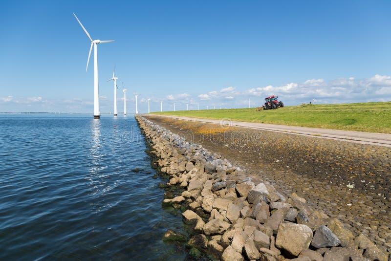 Fila larga de las turbinas de viento de la orilla en el mar holandés imagen de archivo libre de regalías