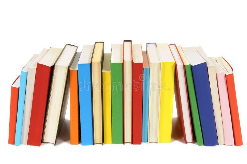 Fila larga de los libros coloridos de la biblioteca aislados en el fondo blanco fotografía de archivo