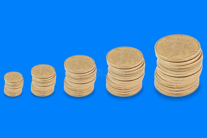 Fila orizzontale delle pile di molte monete gialle da piccolo a grande su fondo blu fotografia stock