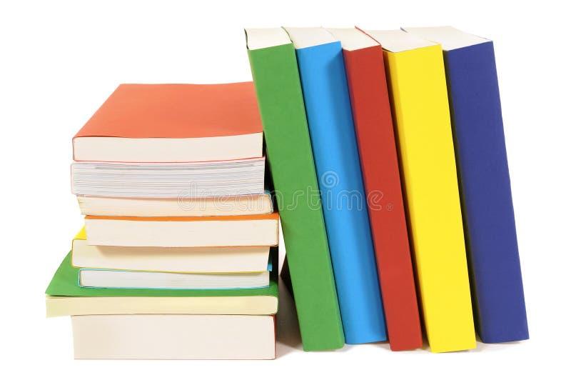 Fila que se inclina de la pequeña pila de los libros coloridos aislados en blanco foto de archivo