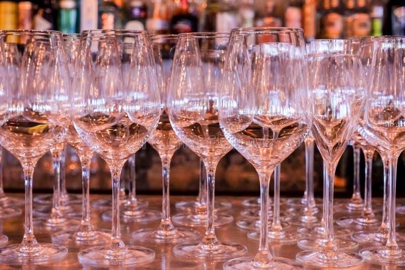 Fila vac?a elegante de copas de vino Mucho vidrio vacío en la barra lista para llenar el vino vidrios limpios en restaurante Vidr imágenes de archivo libres de regalías
