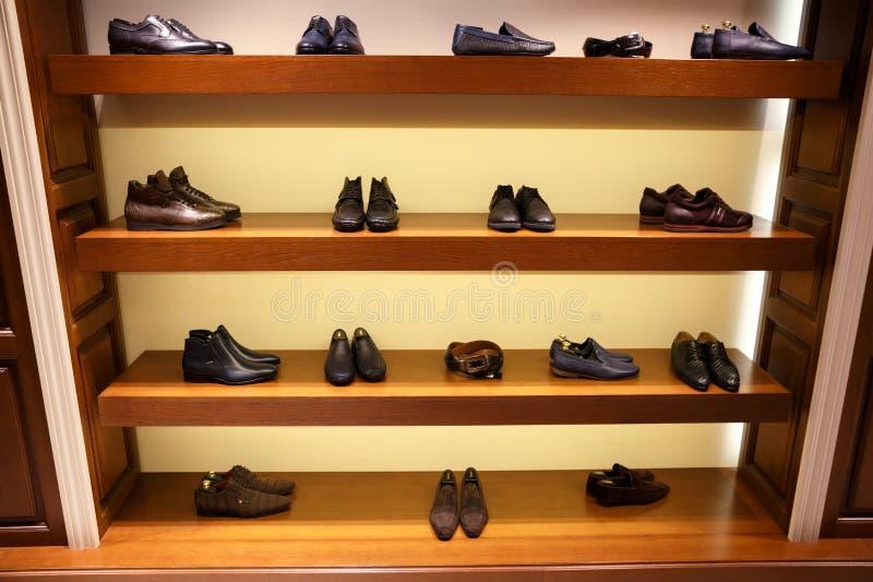 Fila zapatos del ` s del hombre de diversos en cuatro estantes de madera imagenes de archivo