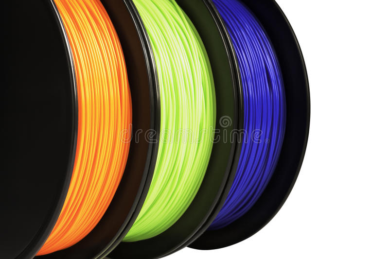 Filament for 3d printing. Bright termoplastic of neon orange, green and blue colors. Isolated on white background. royalty free stock image