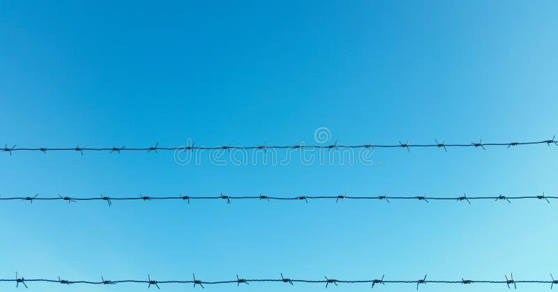 Filamentos del alambre de púas con el cielo azul y las nubes en el fondo imagen de archivo libre de regalías