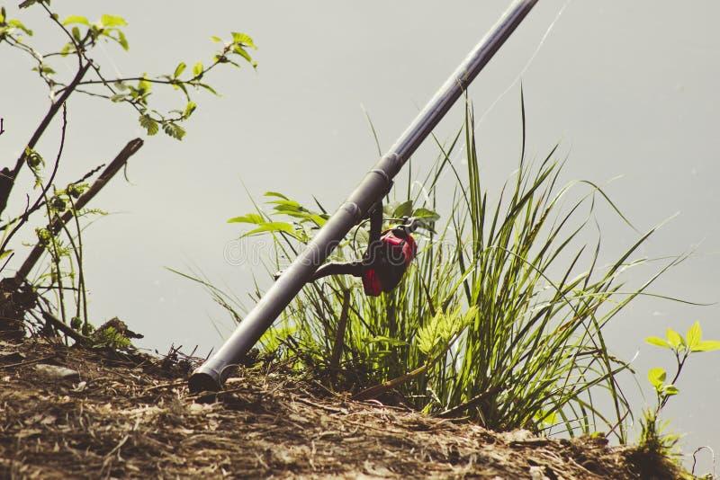 Filando con la bobina sui precedenti di erba verde e di acqua fotografia stock libera da diritti