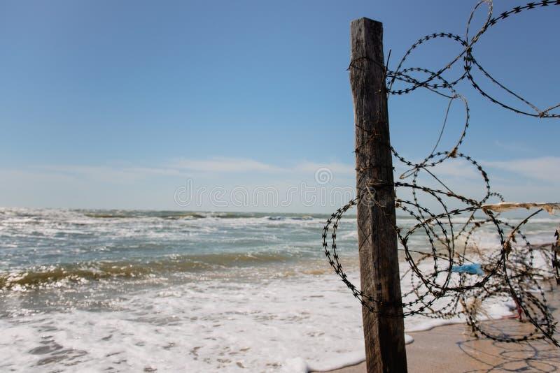 Filar ogrodzenie z drutem kolczastym na plaży zdjęcie stock