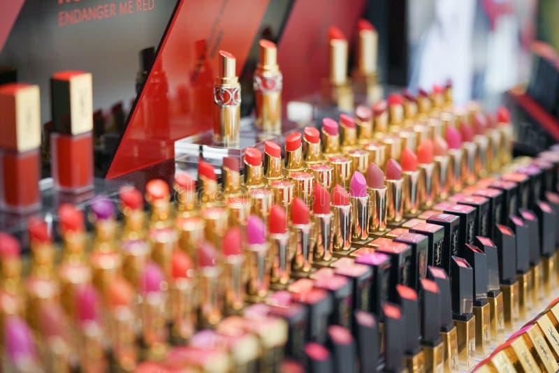 Filas de barras de labios en varios tonos de rojo y de rosado exhibidos en los grandes almacenes Marca de Yves Saint Laurent imágenes de archivo libres de regalías