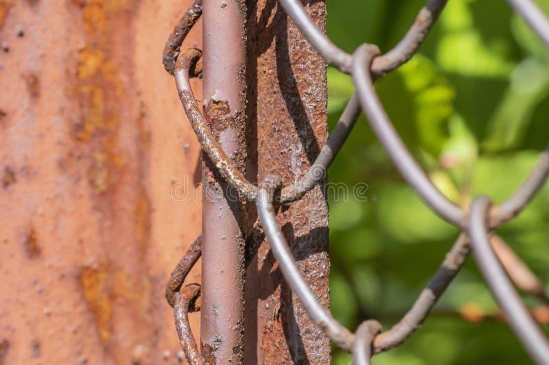 Filas de la malla de alambre y del pilar oxidado del metal de la cerca Textura de la rejilla de la malla de alambre Contexto de G imágenes de archivo libres de regalías