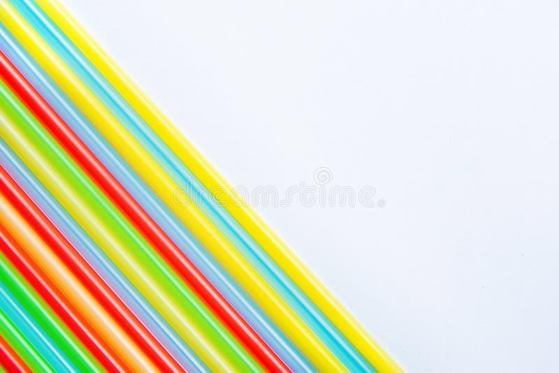 Filas de la paja multicolora de la bebida del arco iris en la composición de la esquina diagonal en fondo del Libro Blanco Diseño fotografía de archivo
