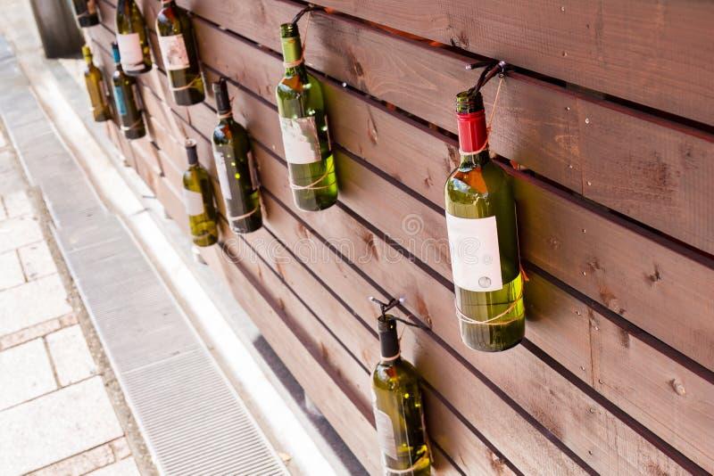 Filas de las botellas de vino que cuelgan en la pared foto de archivo