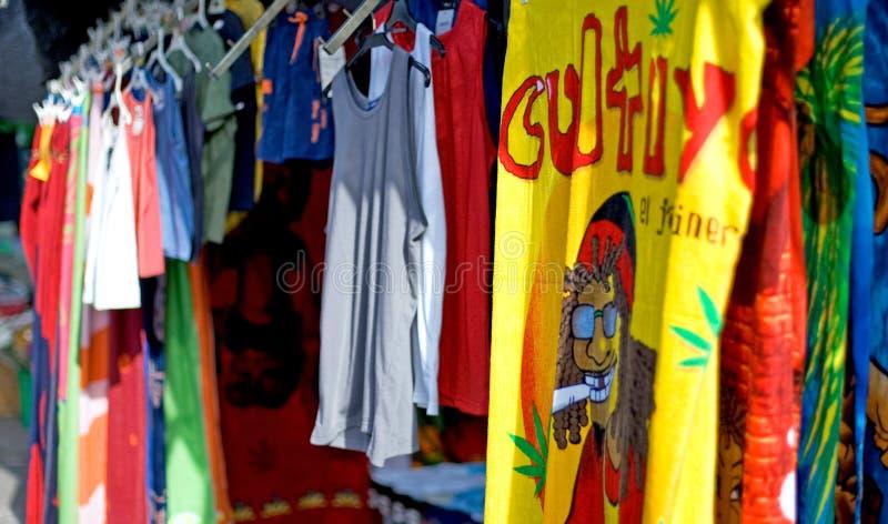 Filas de las camisas de te coloridas para la venta en un mercado de domingo en Spai fotos de archivo