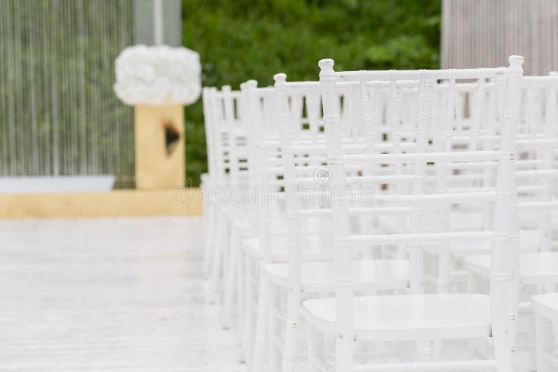 Filas de las sillas blancas vacías que se sientan en un piso de madera Sillas de la boda con las flores en la ceremonia al aire l imágenes de archivo libres de regalías