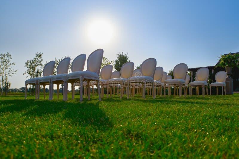 Filas de las sillas vacías blancas en un césped antes de una boda o de una ceremonia fotografía de archivo