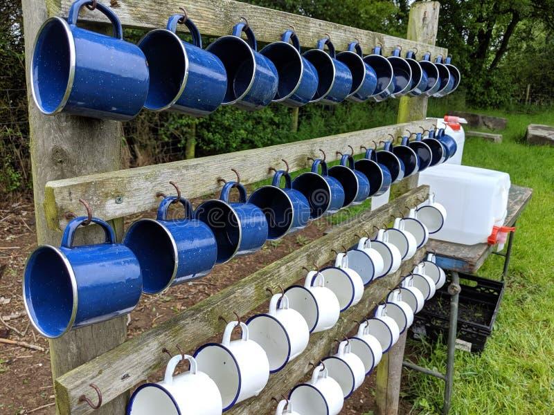 4 filas de las tazas que acampan blancas y azules foto de archivo