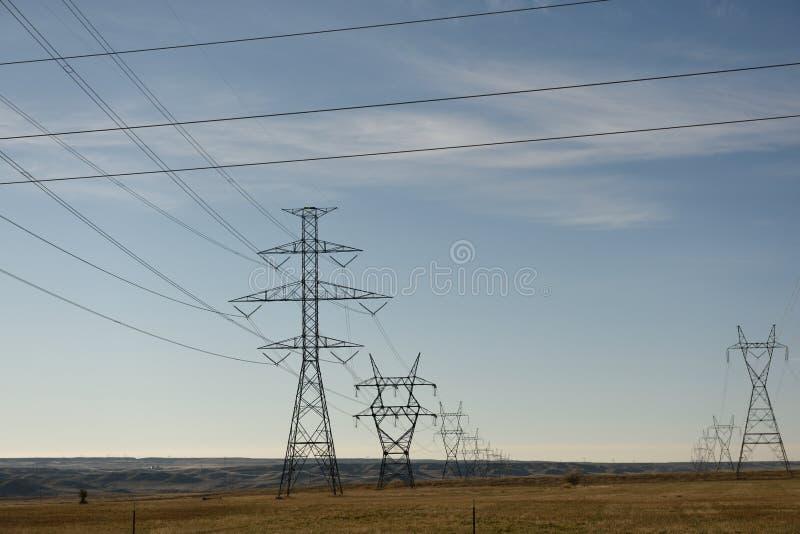 Filas de las torres eléctricas de la rejilla del metal y de las líneas eléctricas de alto voltaje con un cielo azul y un paisaje  fotos de archivo