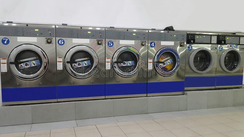 Filas de lavadoras industriales comerciales en la lavandería/la lavandería automática para el uso del ` s del público/del consumi foto de archivo