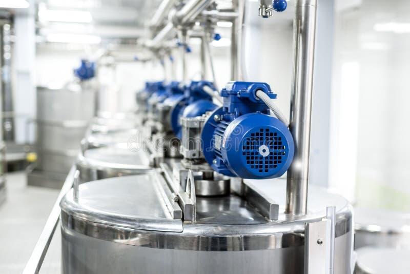 Filas de motores eléctricos azules en los tanques para los líquidos de mezcla imagenes de archivo
