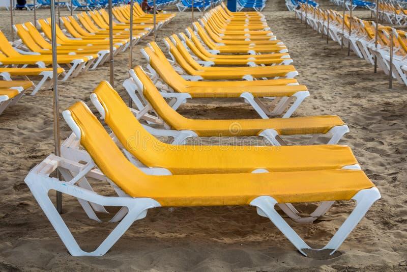 Filas de sunbeds amarillos en la playa Playa de Puerto Rico en las Canarias imagen de archivo