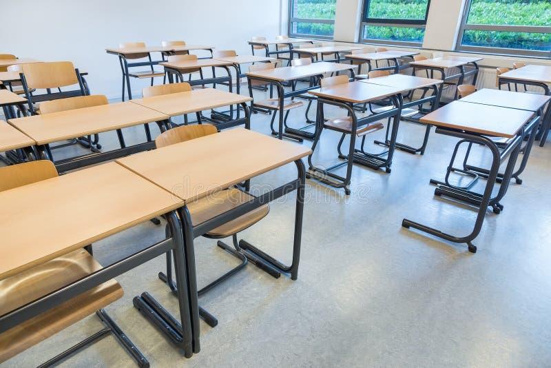 Filas de tablas y de sillas en sala de clase foto de archivo libre de regalías