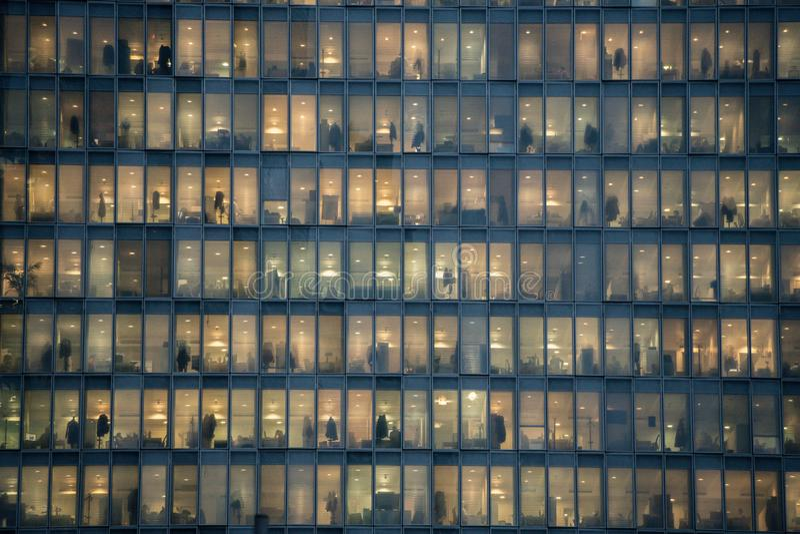 Filas de ventanas con la gente que trabaja dentro de un edificio de oficinas en la noche en Milán, Italia imagen de archivo libre de regalías