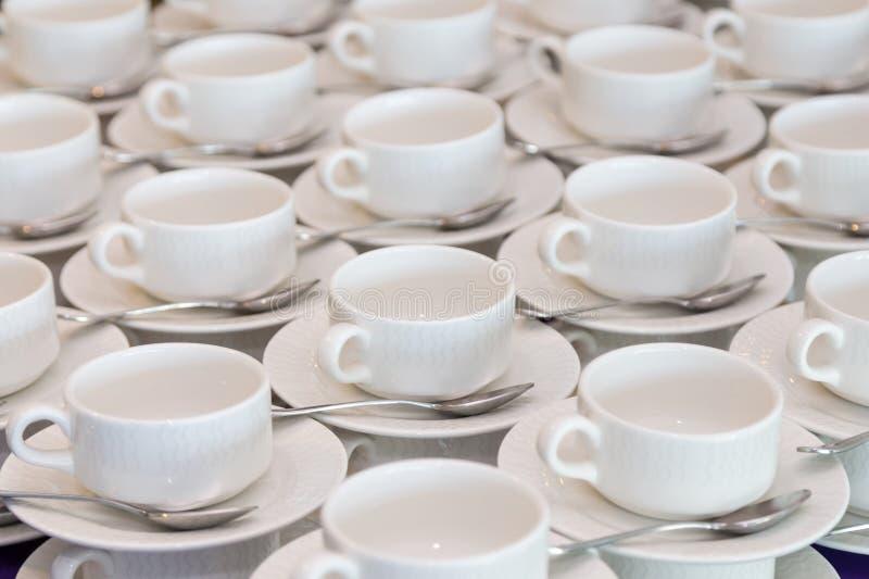 Filas del café con leche o tazas de té limpias, plato y cuchara en una cafetería o un restaurante listo para servir una bebida ca fotos de archivo libres de regalías