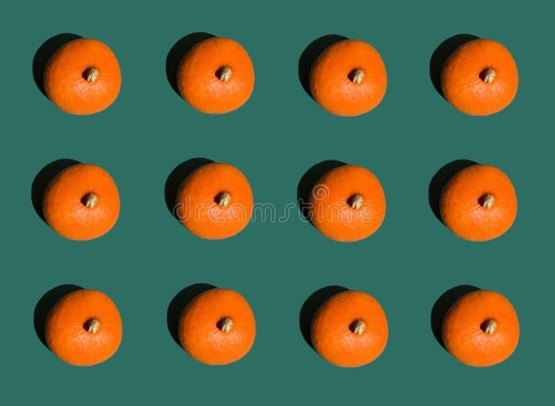 Filas geométricas del fondo de Halloween de calabazas anaranjadas brillantes en verde oscuro Modelo inconsútil estilo del arte po imagen de archivo libre de regalías