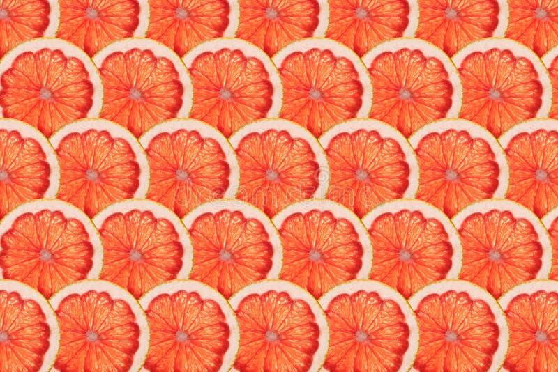 Filas perfectas de las rebanadas maduras del pomelo rosado imagen de archivo