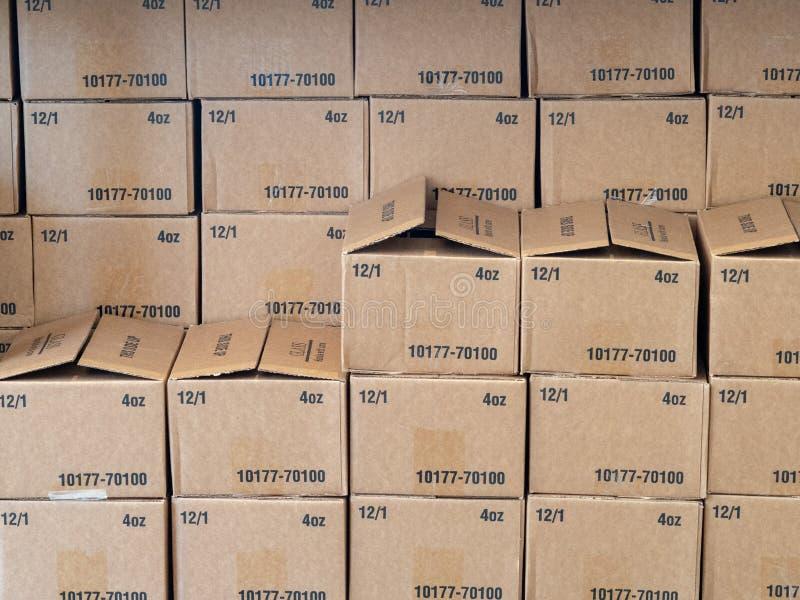 Filas y pilas de cajas de cartón que se sientan dentro de un almacén imagenes de archivo