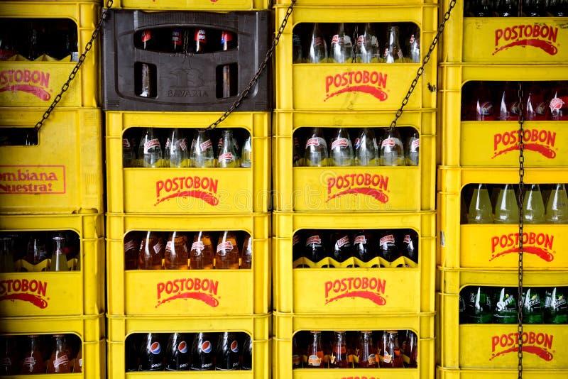 Filas y pilas de cajones y de botellas amarillos de Postobon fotos de archivo