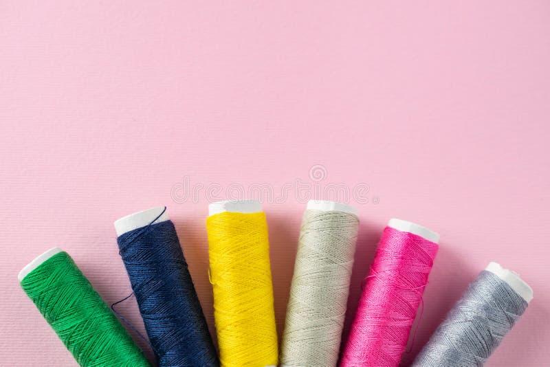 Filati cucirini di colore su fondo rosa immagine stock