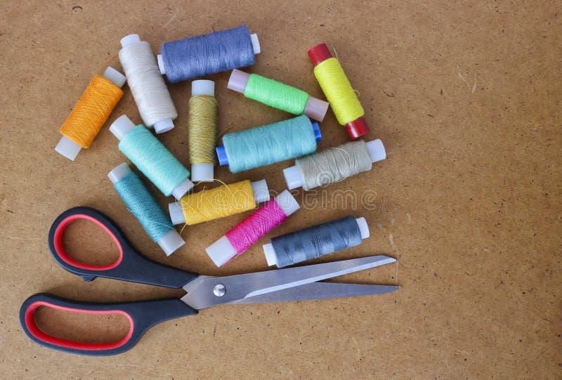 Filati cucirini multicolori su un rotolo per il cucito e l'adattamento delle forbici su un fondo di legno immagini stock libere da diritti