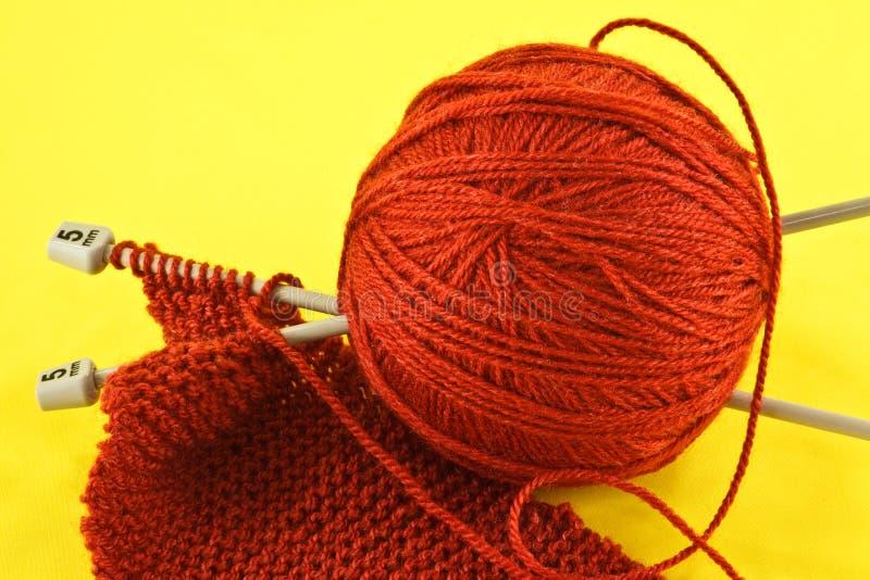 Filato e ferri da maglia arancio fotografia stock