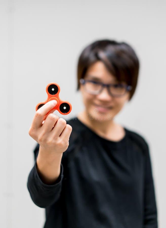 Filatore asiatico di irrequietezza del oragne della tenuta della donna fotografie stock libere da diritti