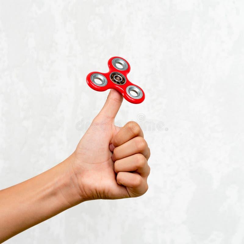 Filatore di irrequietezza Filatore rosso della mano, giocattolo irritantesi della mano che gira sulla mano del ` s del bambino Di immagine stock libera da diritti