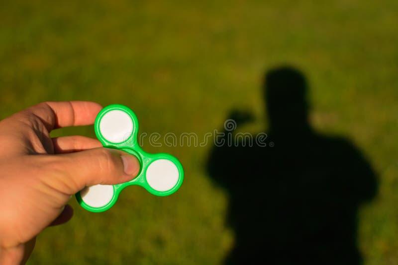 Filatore in mani maschii su un fondo di erba verde e dell'uomo dell'ombra fotografia stock