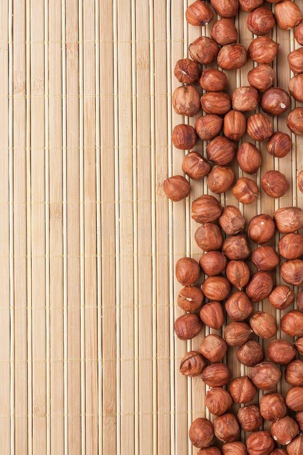 Filbert descascado que encontra-se em uma esteira de bambu fotos de stock royalty free