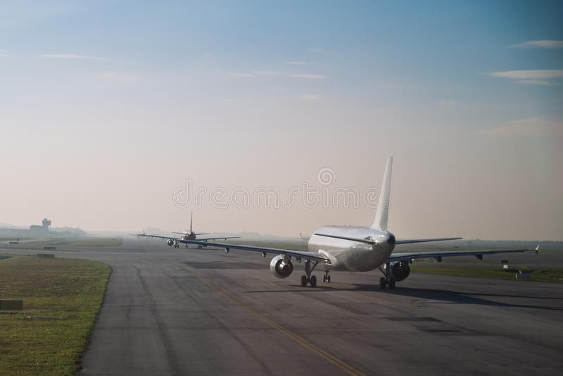 File d'attente commerciale d'avion roulant au sol pour décoller sur la piste image stock