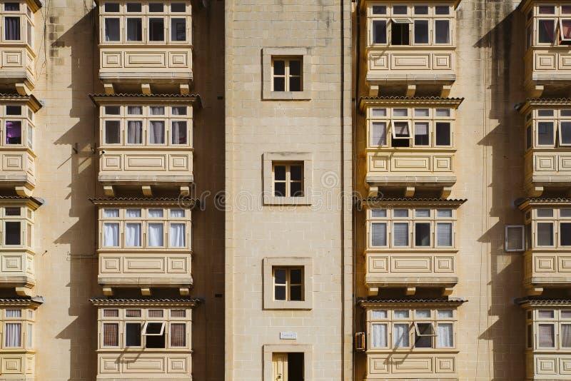 File dei balconi tradizionali maltesi di legno colorati pietra identica alla luce solare dura Alloggio sociale di La Valletta fotografia stock libera da diritti