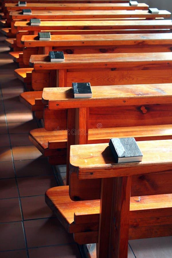 File dei banchi di chiesa con le bibbie Banchi di chiesa di legno vuoti Fuoco selettivo immagini stock