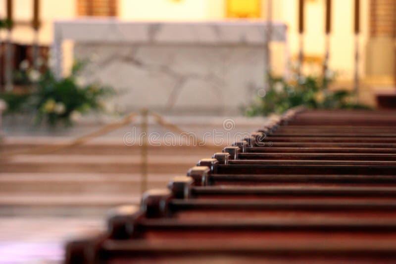 File dei banchi di chiesa Riflessione di luce solare sui banchi di chiesa di legno lucidati Fuoco selettivo fotografia stock libera da diritti