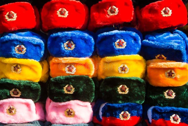 File dei cappelli russi di inverno dei colori differenti con gli emblemi dell'esercito al mercato di strada alla vecchia via di A fotografie stock libere da diritti