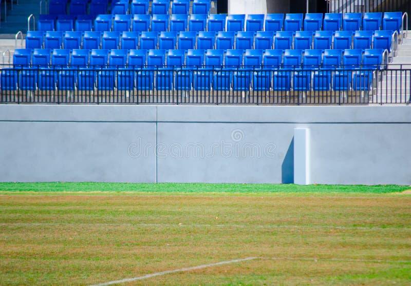 File dei sedili blu vuoti in uno stadio di sport con il campo di erba verde immagini stock libere da diritti