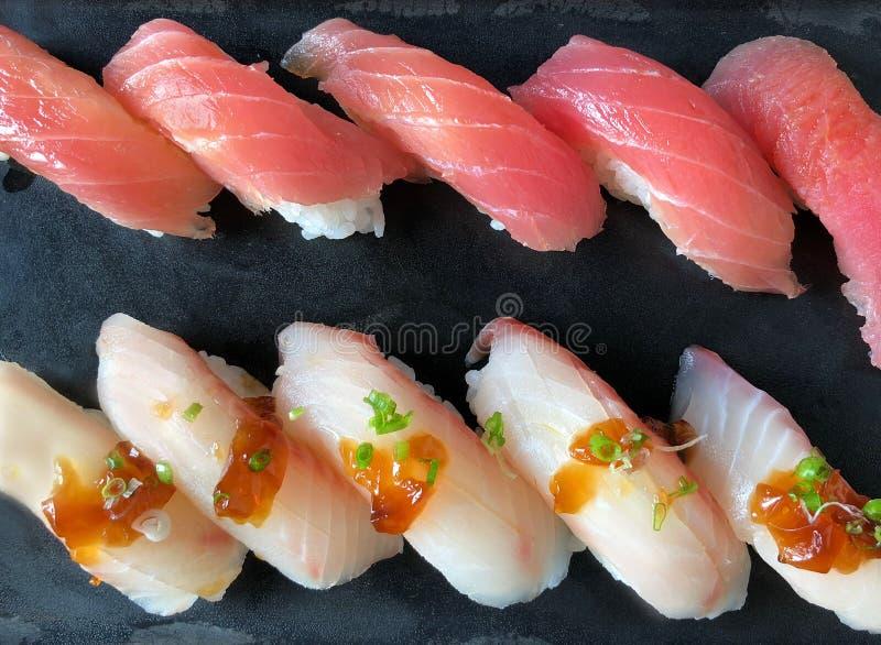 File dei sushi freschi Makuro di Akami Nigiri del giapponese e dei sushi dalla coda gialla di Hamachi Nigiri sul servizio nero de immagini stock