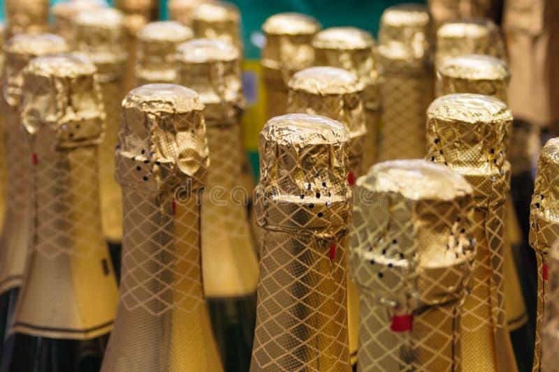 File delle bottiglie con champagne nella stagnola di oro fotografie stock