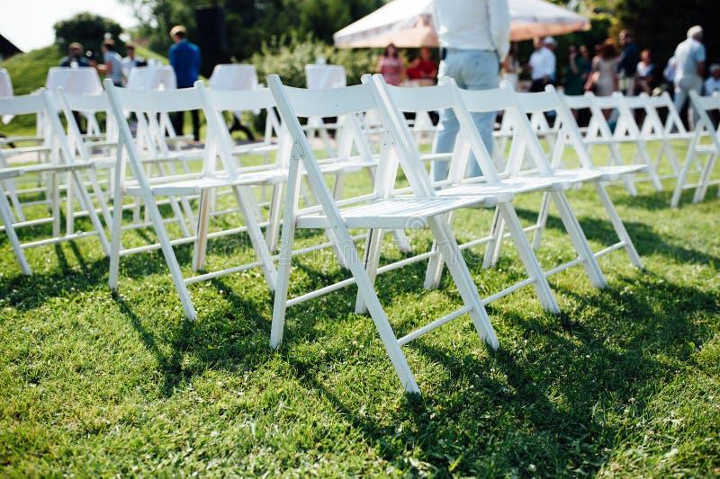 File delle sedie pieghevoli bianche su prato inglese immagine stock