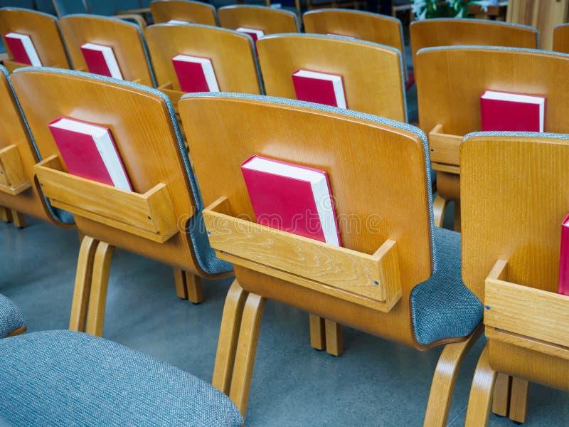 File di sedili con le bibbie nella chiesa fotografie stock