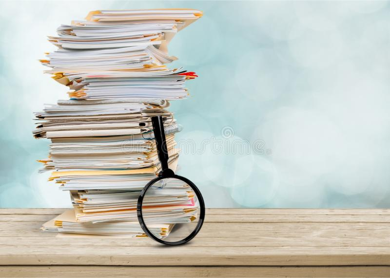 File folders with documents and magnifying glass. File documents folders white background paper glass stock photo